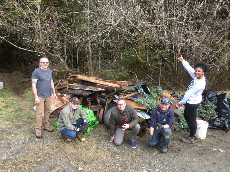 Coast Guard volunteers pose with debris and garbage removed from Switzer Creek riparian.